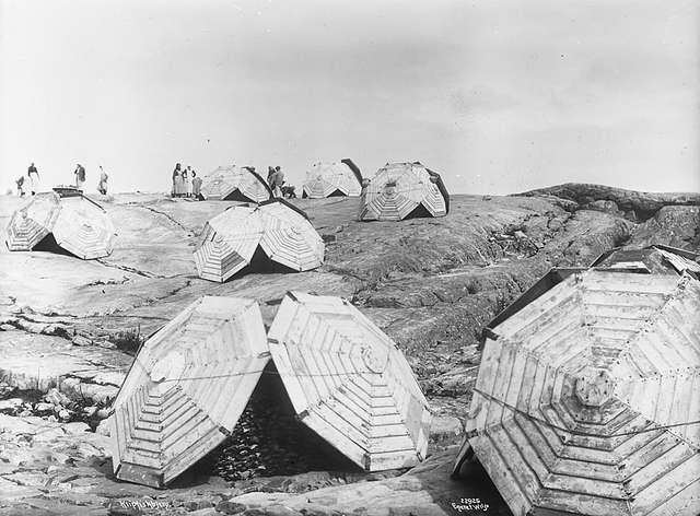 De stapels klipvis onder de houten schermen bij Kristiansund (1922). (Norsk Folkemuseum, foto Anders Beer Wilse)